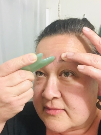 The blogger demonstrates gua sha on forehead lines...