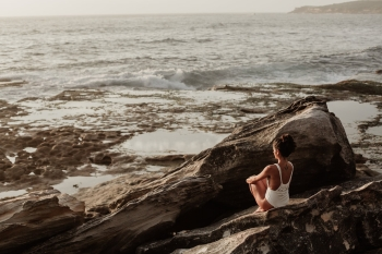 Woman sitting on ocean rocks